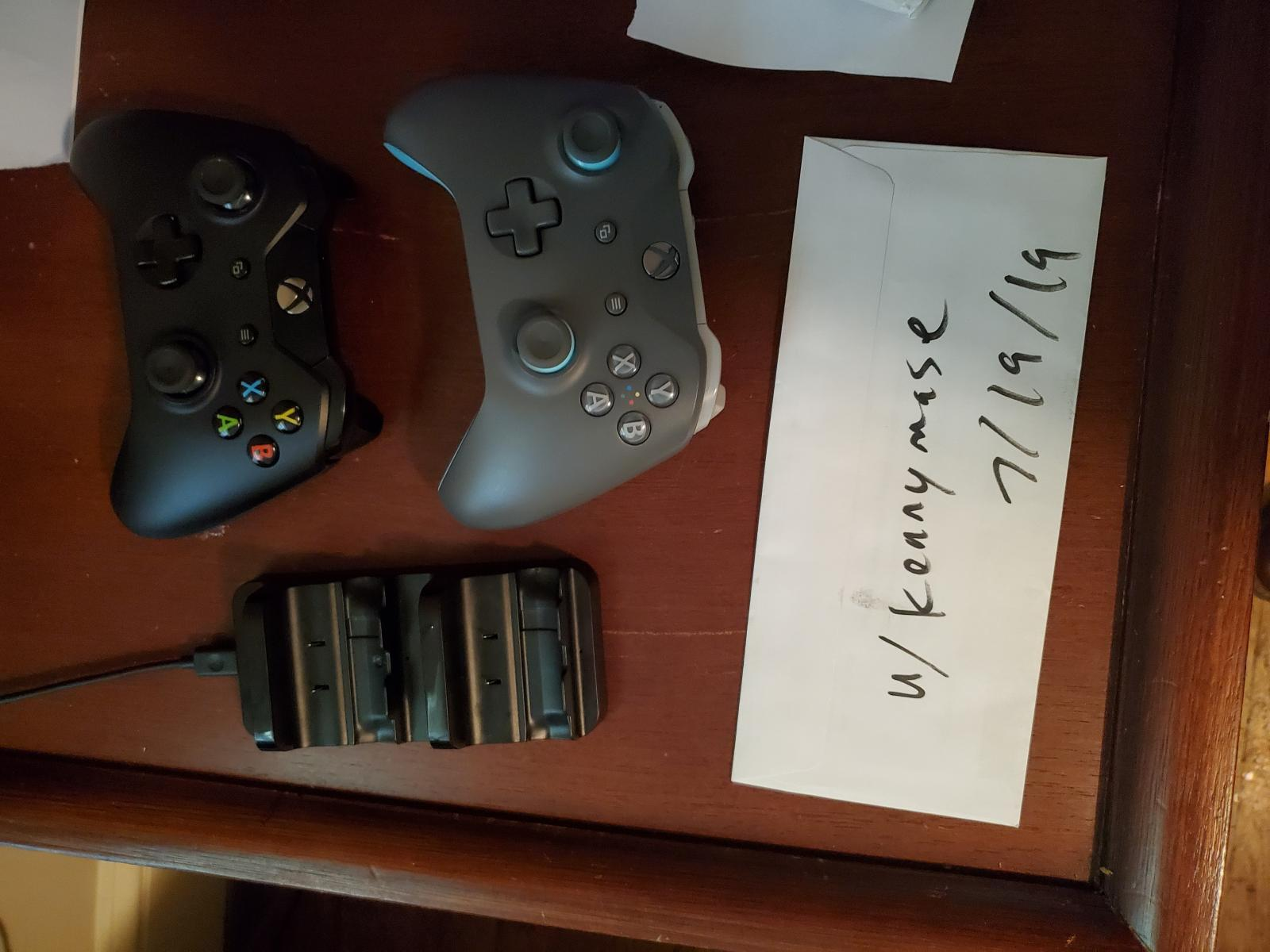 Photo of Xbox One X w/ 2 controllers and charging cradle